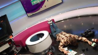 Presenter Ricky Boleto lying face down in the Newsround studio. Various broadcast equipment is scattered on the floor.