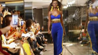 A model walking down a catwalk during African Fashion International Fashion Week in Cape Town, South Africa as people in the crowd take pictures. The model is wearing clothes by UNICEF ambassador and South African designer Gavin Rajah.