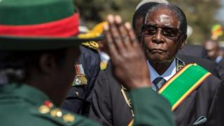 Zimbabwe President Robert Mugabe (R) inspects a guard of honour during official Heroes Day commemorations held at National Heroes Acre in Zimbabwe on August 14, 2017.