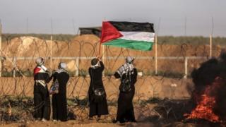 نساء فلسطينيات يحملن العلم الفلسطيني