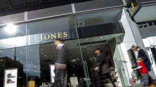 Figures walking past Jones Bootmaker shop