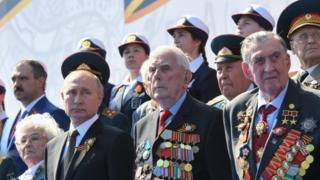 Vladimir Putin and veterans watch a military parade in Moscow on 24 June