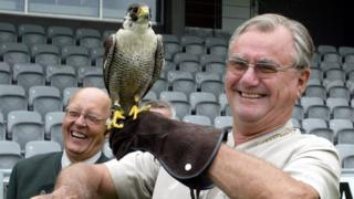 "In this file photo taken on July 8, 2006, Prince consort of Denmark Henrik holds a hawk ""Phoenix 2"" as falconer trainer Frank Skaarup Hansen of Sonderup laughs, before the official opening ceremony of the European Hunting Horn championship held in Horsens, Jutland"