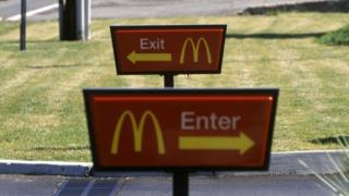 McDonald's enter and exit signs outside a restaurant