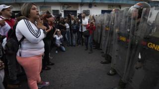 Эта женщина и группа людей пытаются убедить Национальную гвардию Венесуэлы пропустить их на территорию Колумбии