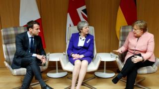 Umukuru w'Ubufaransa Emmaneul Macron (i bubamfu), umushikiranganji wa mbere w'Ubwongereza Theresa May (hagati) n'umuchanceliere w'Ubudage Angela Merkel