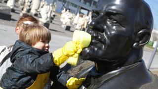 Menino limpa estátua do Lenin na Rússia