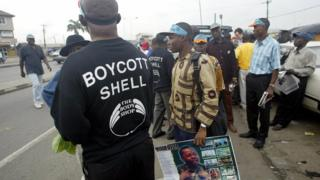A man wearing a T-shirt advocating the boycott of Shell oil stands next to another carrying a poster of Ken Saro-Wiwa during a rally on the Port Harcourt highway 10 November 2005