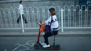 A Chinese woman drives an electric scooter along a street in Beijing