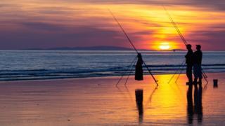 Fishermen on the beach at Tywyn, Gwynedd, with Llyn Peninsula in the distance