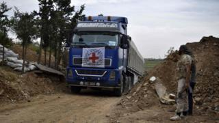 An aid truck of the International Committee of the Red Cross (ICRC) drives past rebel fighters as it enters the rebel-held village of Teir Maalah, on the northern outskirts of Homs in central Syria, on April 25, 2016.