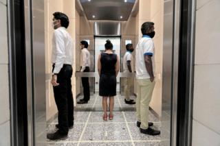 in_pictures People face away from each other as they practise social distancing inside a lift