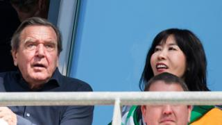 Gerhard Schroeder and his South Korean partner Kim So-Yeon watch the German first division Bundesliga football match between Hannover 96 and Bayern Munich on April 21, 2018.