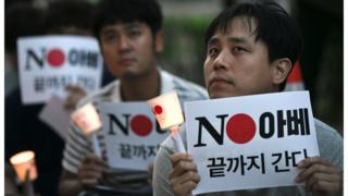 "South Korean protesters hold signs reading ""No Abe"" during a rally in Seoul on 1 August denouncing Japan for its recent trade restrictions against Seoul"