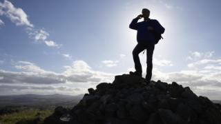 man on phone on top of mountain