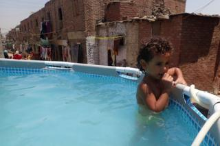 A child holds on to the edge of temporary swimming pool in the Manshiyat Naser, a poor area of Egypt's capital city, Cairo.