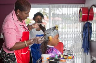 St Claire Adotey does a woman's hair in her salon