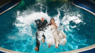 Louise Young and Sam Gilbert jumping into a swimming pool on their wedding day