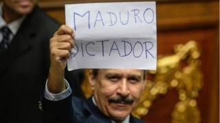 "A Venezuelan opposition deputy holds up a sing reading "" Maduro dictator"" during an extraordinary session of the National Assembly, in Caracas on October 23, 2016."