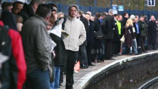 Commuters wait on a railway platform