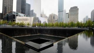 The National September 11 Memorial Museum stands beyond the north reflecting pool