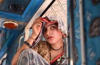 A female migrant worker from Uttar Pradesh sits inside a bus leaving Gujarat after attacks on migrants following the rape of a 14-month-old baby