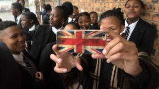 Schoolchildren, one with a phone decorated with the British flag, wait for UK Prime Minister Theresa May at the ID Mkhize Secondary School in Gugulethu, Cape Town, South Africa - Tuesday 28 August 2018