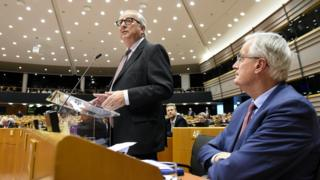 President of the European Union Commission Jean-Claude Juncker (L), flanked by European Chief Brexit negotiator, Michel Barnier (R), speaks during a session of the parliament at the EU headquarters, in Brussels, on January 30, 2019