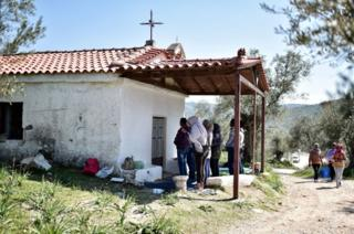 Eritrean and Ethiopian Christian refugees pray outside a small Orthodox church near the Moria hotspot on the Greek island of Lesbos on March 28, 2017