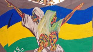 A man, woman and two children depicted on a mural in front of Sudan's old flag - Khartoum, Sudan
