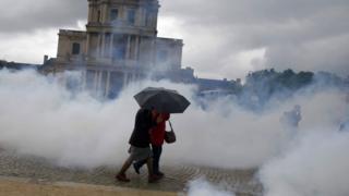 Women walk through a fog of tear gas in Paris
