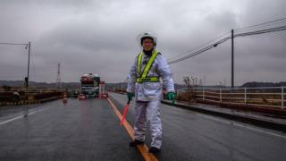 A policeman stands guard at one of the entrances to the 20km evacuation zone surrounding the tsunami-crippled Fukushima Dai-ichi nuclear plant on March 09, 2012 in Minamisoma in Fukushima Prefecture,