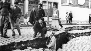 Hombres entre las grietas causadas en el suelo en el terremoto de Valdivia, Chile, en 1960