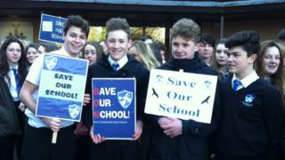 pupils hold Save Our School banners at a protest outside the council offices
