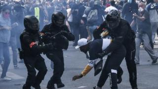 French riot police forces detain a protester during a rally as part of the