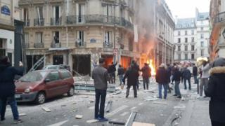 Flames are visible at the site of the bakery as people in the street survey the destruction