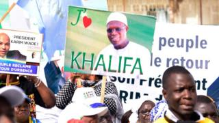 Supporters of Khalifa Sall hold placards expressing their love for him in a May 2019 protest