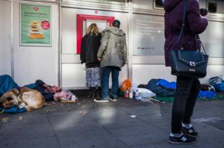 People take cash out next to a homeless person