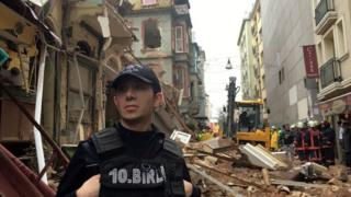 A police officer guards near the collapsed building as firefighters work at the scene in Istanbul
