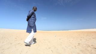 Gambian national Ebrima Sanneh, who has been in exile since 2013, walks on a beach in Dakar, Senegal, December 5, 2016.