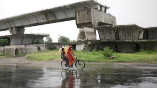 A woman on a bicycle rides in heavy rain