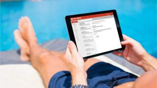 Using a tablet to read emails while sitting by a swimming pool