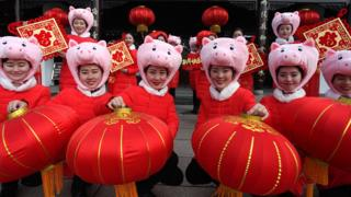 People wearing pig hats holding red lanterns