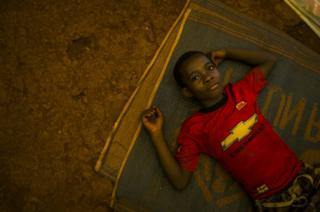 A young Congolese refugee lays on a mat on the ground in a mass shelter in the Nyarugusu refugee camp in Tanzania, March 2016