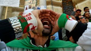 Algerian protestors shout slogans during a demonstration.