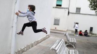 Kilian, 6, wears a protective face mask as he jumps from a bench, after restrictions were partially lifted for children, during the coronavirus disease (COVID-19) outbreak, in Igualada, Spain April 26, 2020.