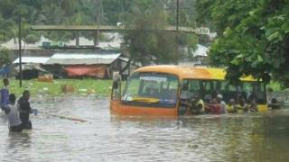 Zanzibaris pulling a bus stuck following flooding on the islands of Zanzibar