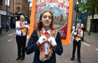 A young woman wearing an Orange Order sash with two Orangemen carrying a banner behind her