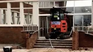 Экскаватор разламывает двери в отель