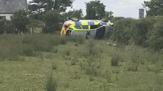 The car on its side in a field